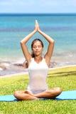 Yoga woman meditation by sea. Doing the Sukhasana, easy pose. Woman meditating in beautiful ocean landscape retreat. Beautiful young mixed race Asian Caucasian Royalty Free Stock Photos