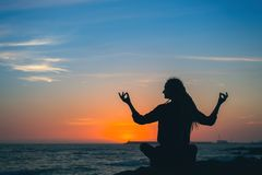 Yoga woman meditation silhouette. Healthy lifestyle on the ocean during amazing sunset royalty free stock images