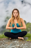 Yoga woman on mountain. Young woman doing yoga on the summit of the mountain Royalty Free Stock Image