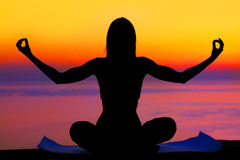 Yoga woman over sunset. Healthy woman doing yoga outdoor, sunset over sea, body care & meditation concept Royalty Free Stock Photo