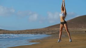 Yoga woman poses at beach working out and relaxing outside on beach at sunrise. Female yoga girl working out training in stock footage