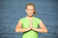 Yoga woman prayer close up. A woman meditating by the water Stock Photos