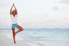 Yoga woman on sea coast Stock Photos