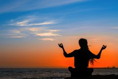 Yoga woman silhouette on the ocean during amazing sunset stock image