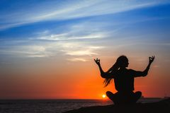 Yoga woman silhouette series. Meditation during amazing sunset. Yoga woman silhouette series. Meditation on the ocean during amazing sunset stock image