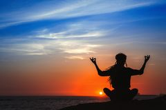 Yoga woman silhouette series. Meditation. Yoga woman silhouette series. Meditation on the ocean during amazing sunset stock image