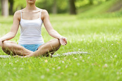 Yoga woman siting on grass meditaiting in lotus position. Stock Photos