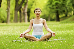 Yoga woman siting on grass relax. Royalty Free Stock Image