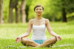Yoga woman siting on grass relax. Stock Photo