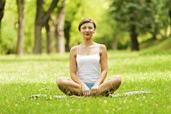 Yoga woman siting on grass relax and smiling. Royalty Free Stock Image
