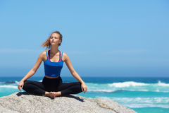Yoga woman sitting alone by the sea Royalty Free Stock Photography