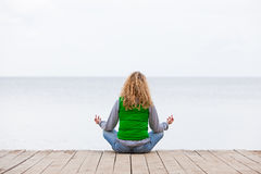 Yoga woman sitting back on ocean bridge Stock Images