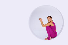Yoga woman   sitting in geometric  sphere. Beautiful and sporty woman  in  active wear,  sitting in geometric  design of round shapes,in sphere Royalty Free Stock Image