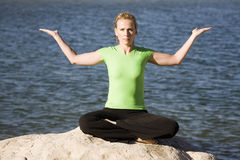 Yoga woman sitting hands up by water. A woman sitting on a rock by the water doing yoga Royalty Free Stock Photo