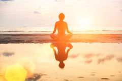Yoga woman sitting in lotus pose on the beach during sunset. Royalty Free Stock Photos