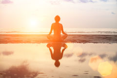 Yoga woman sitting in lotus pose on the beach during sunset Stock Photography