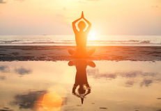 Yoga woman sitting in lotus pose on the beach during sunset, with reflection in water. Royalty Free Stock Photo