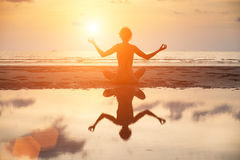 Yoga woman sitting in lotus pose on the beach during sunset Royalty Free Stock Photography