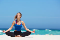 Yoga woman sitting in lotus position on the beach Stock Image