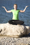 Yoga woman sitting palm up by water. A woman sitting on a rock while doing yoga position Stock Photos