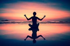 Yoga woman sitting on sea coast at sunset. Religion. Stock Images