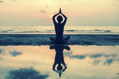 Yoga woman sitting on sea coast at sunset Royalty Free Stock Photography