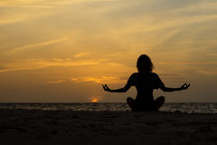 Yoga woman sitting on sea coast at sunset. Royalty Free Stock Image