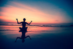Yoga woman sitting on sea coast Royalty Free Stock Photos