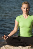 Yoga woman sitting by water close up Royalty Free Stock Images