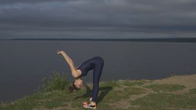 Yoga woman in sportswear, energy concentration. Yoga woman in sportswear and sneakers, energy concentration against lake, side view. Yogi training, outdoor stock footage