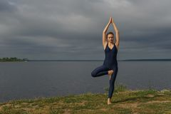 Yoga woman in sportswear pose against lake stock image