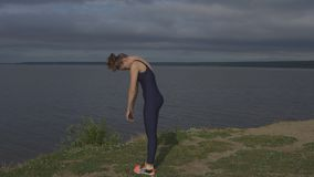 Yoga woman in sportswear, energy concentration. Yoga woman in sportswear and sneakers, energy concentration against lake, side view. sport, yogi, meditation and stock footage