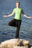 Yoga woman standing on one leg by water. A women doing the yoga position tree while standing on a rock by the deep blue water Stock Photos