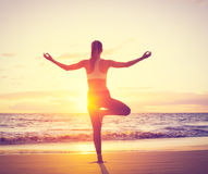Yoga Woman at Sunset. Silhouette of young woman practicing yoga on the beach at sunset Stock Images