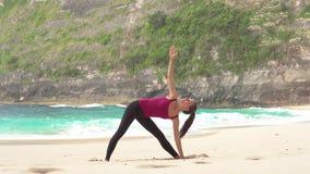 Yoga woman. Trikonasana pose. Ocean background. Yoga woman. Trokonasana pose. Ocean lagoon background stock video