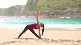 Yoga woman. Trikonasana pose. Ocean background. Yoga woman. Trokonasana pose. Ocean lagoon background stock footage
