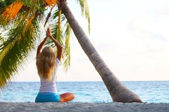 Yoga woman under palm Stock Images