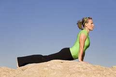Yoga woman up dog. A woman doing the yoga position upward dog on a rock in the outdoors Stock Photography