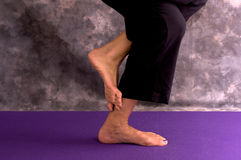 Yoga womans feet in eagle pose asana Royalty Free Stock Images