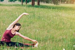Yoga y meditación en naturaleza en un día soleado Mujer hermosa en el top de Borgoña en el fondo de campos y de bosques imagen de archivo libre de regalías