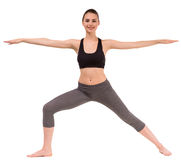 Yoga. Young dark haired slim woman doing yoga exercise, stretching her arms to the side Stock Photo