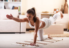 Yoga. Young woman doing yoga in her living room Royalty Free Stock Photography