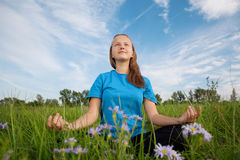Yoga young woman on green grass Royalty Free Stock Images