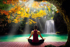 Yoga. Young woman in yoga pose sitting near watefall, Rear view Stock Photography