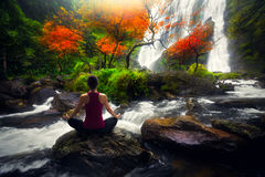Yoga. Young woman in yoga pose sitting near watefall, Rear view Royalty Free Stock Photo