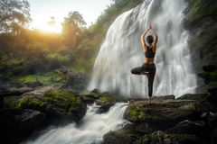 Yoga. Young woman in a yoga pose at the waterfall Royalty Free Stock Images