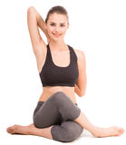 Yoga. Young woman sitting in yoga pose, looking at camera and smiling Stock Photography