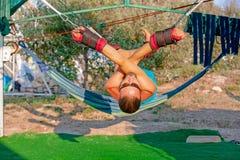 Yogabehandlung für Kern, Yogaschwingen, dünner junger Mann gegurtet zu vier Planken über dem Boden, sich entwickelnde Ausdauer de stockbilder