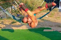 Yogabehandlung für Kern, Yogaschwingen, dünner junger Mann gegurtet zu vier Planken über dem Boden, sich entwickelnde Ausdauer de lizenzfreie stockbilder