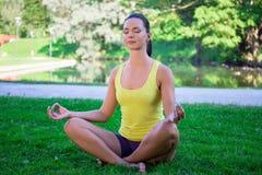 Yogaconcept - de jonge vrouwenzitting in lotusbloem stelt in park Royalty-vrije Stock Fotografie